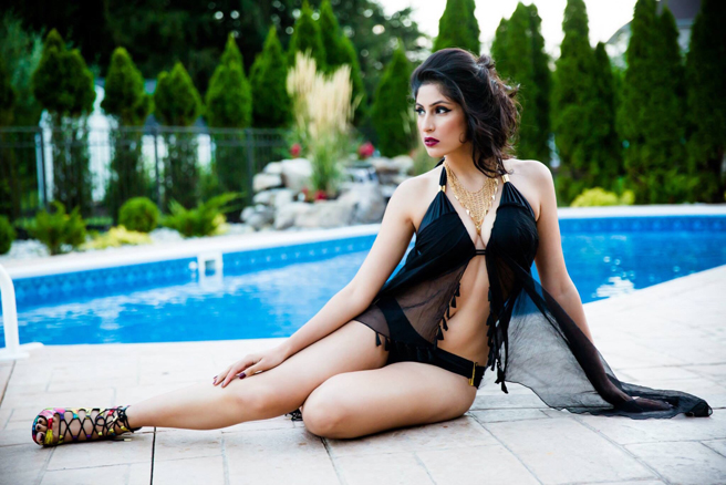 New York based beautiful Divya Sethi wearing an elegant black swimsuit with a gold necklace